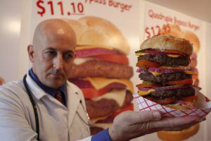 Heart Attack Grill owner Jon poses with a quadruple bypass cheese burger in Chandler, Arizona June 17, 2009. The restaurant is known for its hospital theme and triple and quadruple bypass burgers. REUTERS/Joshua Lott (UNITED STATES) - RTR24RS3